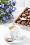 Tasse de café sur un fond blanc avec des un grand choix des chocolats dans une boîte en bois Photo stock