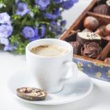 Tasse de café sur un fond blanc avec des un grand choix des chocolats dans une boîte en bois Photos libres de droits