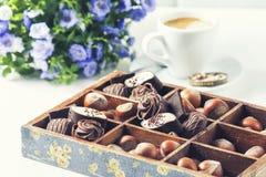 Tasse de café sur un fond blanc avec des un grand choix des chocolats dans une boîte en bois Images stock