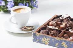 Tasse de café sur un fond blanc avec des un grand choix des chocolats dans une boîte en bois Photographie stock libre de droits