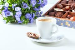 Tasse de café sur un fond blanc avec des un grand choix des chocolats dans une boîte en bois Photos stock