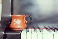 Tasse de café sur un vieux clavier de piano tout en composant Temps de soirée et quelques rayons du soleil Tasse de café sur le c Photo stock