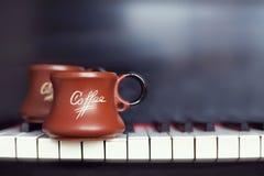 Tasse de café sur un vieux clavier de piano tout en composant Temps de soirée et quelques rayons du soleil Tasse de café sur le c Photo libre de droits