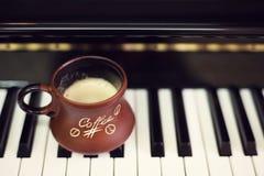 Tasse de café sur un vieux clavier de piano tout en composant Temps de soirée et quelques rayons du soleil Tasse de café sur le c Image libre de droits