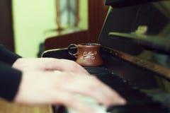 Tasse de café sur un vieux clavier de piano tout en composant Temps de soirée et quelques rayons du soleil Tasse de café sur le c Photos libres de droits