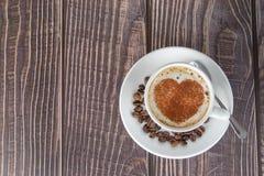 Tasse de café sur une table en bois, avec la poudre de cacao formant un coeur sur la mousse photo stock