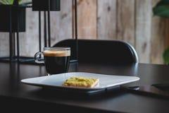 Tasse de café sur une table noire avec un biscuit d'un plat pour le petit déjeuner images stock