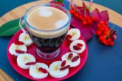 Tasse de café transparente avec la mousse sur une soucoupe rouge image libre de droits
