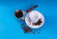 Tasse de café vide avec une soucoupe dans les haricots avec un pot de café de brassage à côté de lui sur un fond bleu photographie stock libre de droits