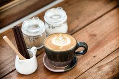 Tasse de caf? d'art de latte avec le pot de sucre sur la table en bois pendant le temps de pause-caf? ? l'arri?re-plan de caf? images libres de droits