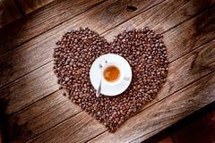Tasse de café sur des grains de café de forme de coeur Images stock