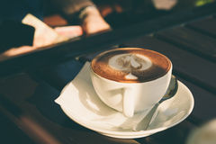Tasse de cappuccino avec de la cannelle sur une table en bois dans un café photographie stock libre de droits