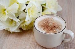 Tasse de cappuccino avec des fleurs Photographie stock