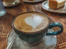 Tasse de cappuccino avec l'art de latte sur un fond en bois brun Mousse élégante, rétro tasse de café dans un café, l'espace de c Image stock