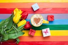 Tasse de cappuccino avec la forme de coeur et bouquet des tulipes Photographie stock libre de droits