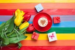 Tasse de cappuccino avec la forme de coeur et bouquet des tulipes Image stock