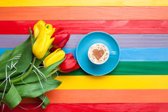 Tasse de cappuccino avec la forme de coeur et bouquet des tulipes Image libre de droits