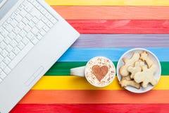 Tasse de cappuccino avec la forme et l'ordinateur de coeur Image stock