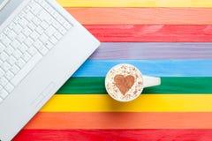Tasse de cappuccino avec la forme et l'ordinateur de coeur Photos stock