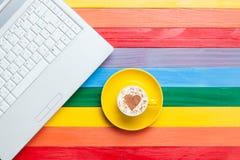 Tasse de cappuccino avec la forme et l'ordinateur de coeur Photographie stock libre de droits