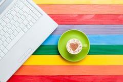 Tasse de cappuccino avec la forme et l'ordinateur de coeur Images stock