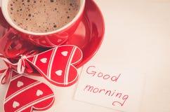 Tasse de cappuccino avec le coeur en bois et bonjour de notes Photo stock