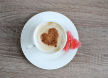 Tasse de cappuccino avec le modèle de coeur de la cannelle Photographie stock libre de droits