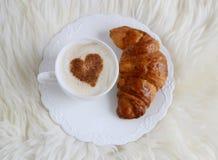 Tasse de cappuccino avec le modèle de coeur de la cannelle et du croissant Photos stock