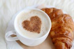 Tasse de cappuccino avec le modèle de coeur de la cannelle et du croissant Image libre de droits