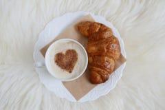 Tasse de cappuccino avec le modèle de coeur de la cannelle et du croissant Photo stock