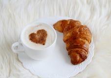 Tasse de cappuccino avec le modèle de coeur de la cannelle et du croissant Photographie stock libre de droits