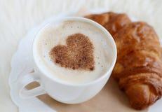 Tasse de cappuccino avec le modèle de coeur de la cannelle et du croissant Photo libre de droits
