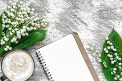 Tasse de cappuccino avec les fleurs du muguet de ressort et le carnet rayé Images libres de droits