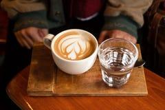 Tasse de cappuccino chaud et verre de l'eau sur la table en bois Image libre de droits