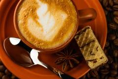 Tasse de cappuccino, de gaufrette de lait-chocolat et de grains de café Image stock