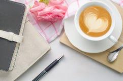 Tasse de carnets, de stylo et de café avec la fleur rose sur b en bois blanc Photographie stock