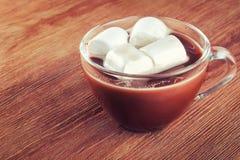 Tasse de chocolat chaud avec des guimauves sur le fond en bois Photographie stock