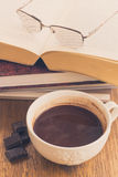 Tasse de chocolat sur la surface en bois avec des livres Images stock