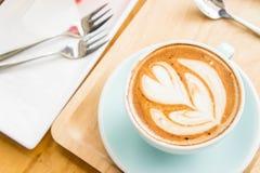 Tasse de coeur de café sur la table en bois en café de boutique de coffe Image stock