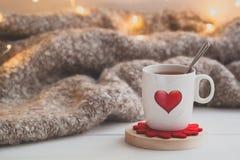 Tasse de fête de thé avec de la fumée et un coeur rouge au-dessus du plaid tricoté photographie stock