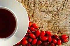 Tasse de fond de Rose Hips Tea On Wooden photographie stock libre de droits