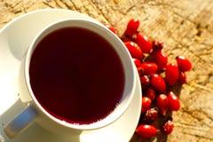 Tasse de fond de Rose Hips Tea On Wooden photos stock