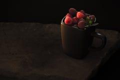 Tasse de framboises mûres sur le fond noir Image libre de droits