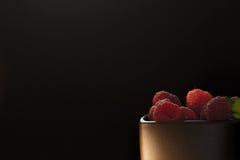 Tasse de framboises mûres sur le fond noir Photographie stock libre de droits
