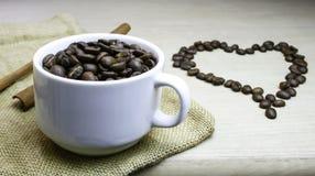 Tasse de grains de café avec des grains de café de coeur Photo stock