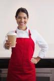 Tasse de jeune barman heureux de café de offre à aller photographie stock libre de droits