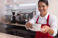 Tasse de jeune barman heureux de café de offre souriant à l'appareil-photo photos stock