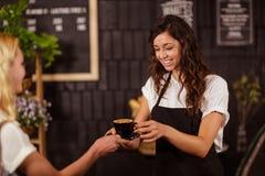 Tasse de jolie serveuse de café de offre au client photographie stock libre de droits