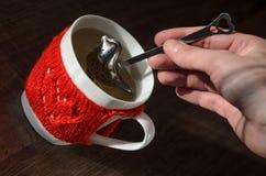 Tasse de laine tricotée par rouge avec le modèle de coeur photos stock