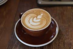 Tasse de latte chaud de café avec le beau style sur la table en bois à dedans Photo stock
